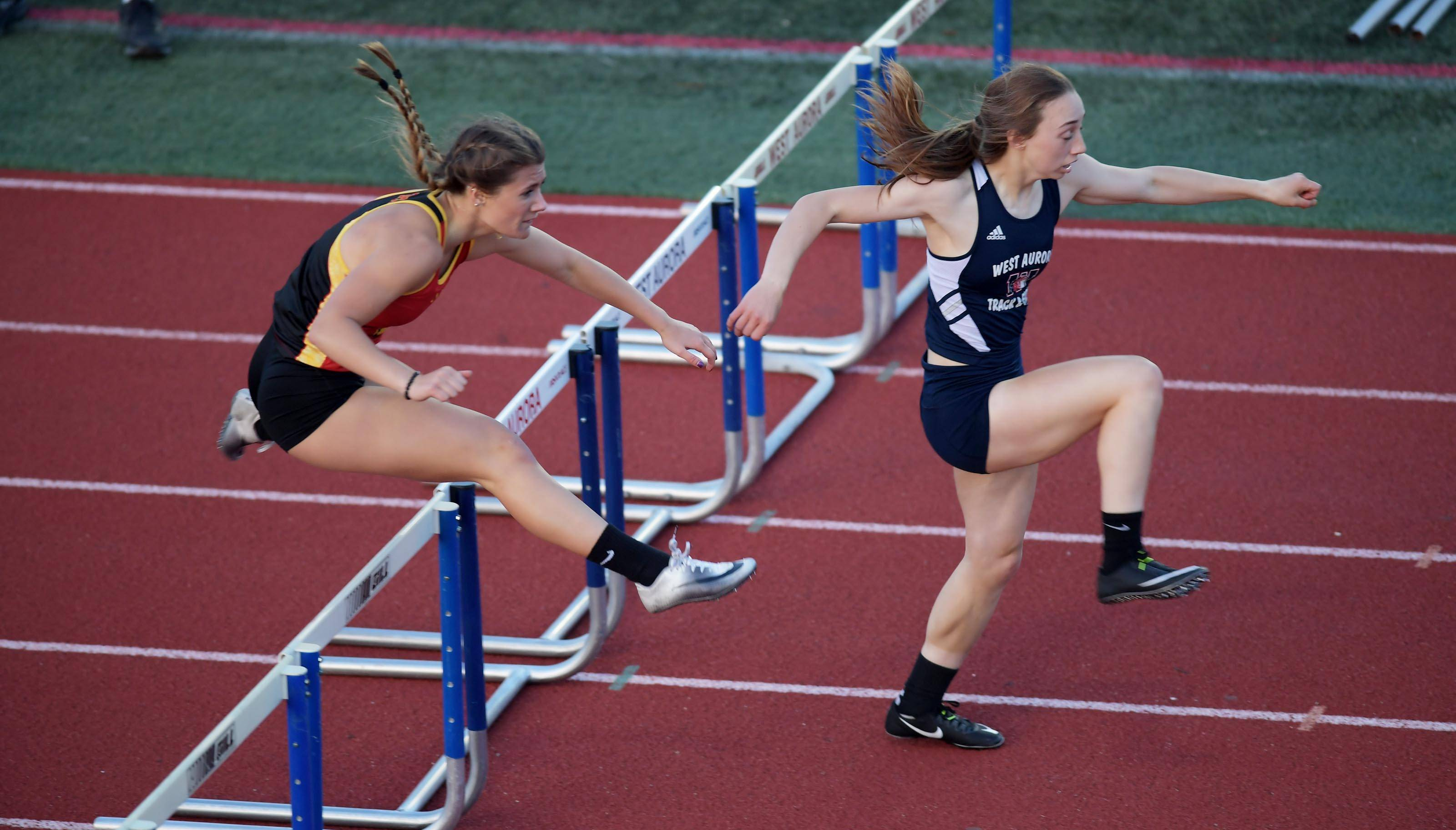 West Aurora's Victoria Spagnola leads Batavia's Sabrina Schlenker in the 300 meter hurdles at the West Aurora girls sectional track meet last Thursday.