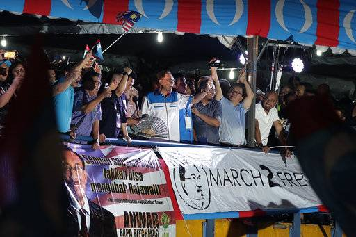 "Malaysia's reformist icon Anwar Ibrahim, center, gestures to his supporters during a rally in Petaling Jaya, Malaysia, Wednesday, May 16, 2018.  Reformist icon Anwar Ibrahim celebrated a ""new dawn"" for Malaysia after he was given a royal pardon and freed from custody Wednesday, transforming a political prisoner into a prime minister-in-waiting following his alliance's stunning election victory."
