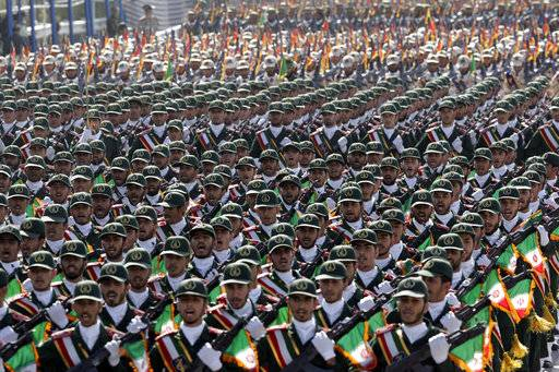 FILE - In this Sept. 21, 2012 file photo, Iran's Revolutionary Guard troops march during a military parade commemorating the start of the Iraq-Iran war 32 years ago, in front of the mausoleum of the late revolutionary leader Ayatollah Khomeini, just outside Tehran. The modern Middle East has been plagued by ruinous wars: country versus country, civil wars with internecine and sectarian bloodletting, and numerous eruptions centered in the Israeli-Palestinian conflict. But never in the last 70 years have they seemed as interconnected as now with Iran and Saudi Arabia vying for regional control, while Israel also seeks to maintain a military supremacy of its own.