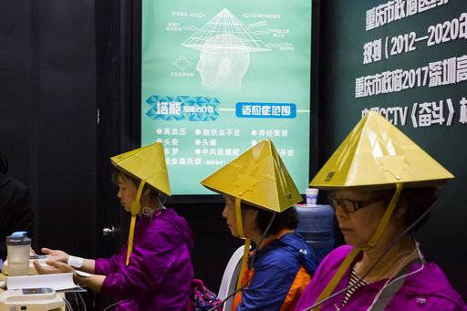 Chinese women try out a pyramid-shaped device purported to improve blood circulation in the brain during the 21st China Beijing International High-tech Expo in Beijing, China, Thursday, May 17, 2018. The annual exhibition is a showcase of China's state-of-the-art technologies and cutting-edge ideas.