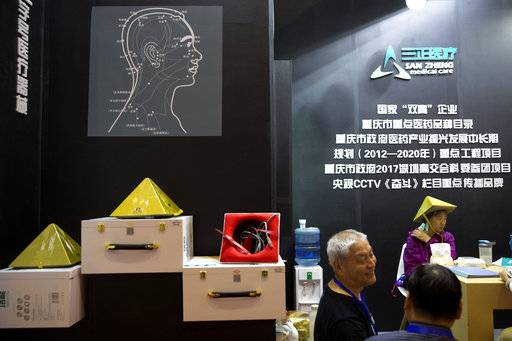 A woman try out a pyramid-shaped device purported to improve blood circulation in the brain during the 21st China Beijing International High-tech Expo in Beijing, China, Thursday, May 17, 2018. The annual exhibition is a showcase of China's state-of-the-art technologies and cutting-edge ideas.