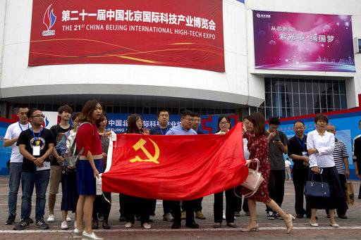 Visitors to the 21st China Beijing International High-tech Expo pose for photos with a Chinese flag in Beijing, China, Thursday, May 17, 2018. The Trump administration has threatened to impose tariffs on up to $150 billion in Chinese imports to punish Beijing over trade practices requiring American companies to hand over technology in exchange for access to the Chinese market. China has counterpunched by targeting $50 billion in U.S. products.