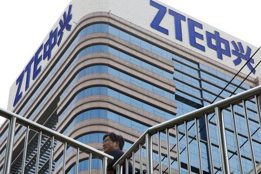 In this photo taken May 8, 2018, a man walks past a building with the ZTE logos in Beijing. As Chinese officials prepare to hold talks with their counterpart in Washington the two countries are reportedly attempting a swap: Relief for ZTE in return for Beijing dropping plans to impose tariffs on U.S. farm products.
