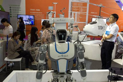 Visitors to the 21st China Beijing International High-tech Expo look at robots and helicopter drone displayed in Beijing, China, Thursday, May 17, 2018. The Trump administration has threatened to impose tariffs on up to $150 billion in Chinese imports to punish Beijing over trade practices requiring American companies to hand over technology in exchange for access to the Chinese market. China has counterpunched by targeting $50 billion in U.S. products.