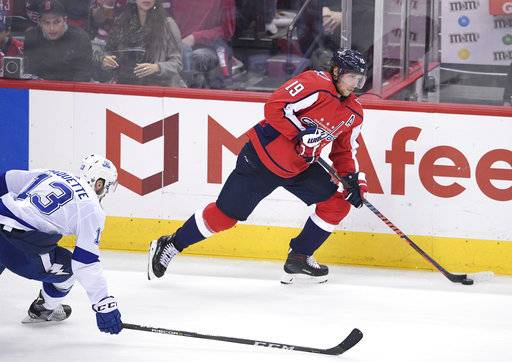 Washington Capitals center Nicklas Backstrom (19), of Sweden, skates with the puck past Tampa Bay Lightning center Cedric Paquette (13) during the second period of Game 4 of the NHL hockey Eastern Conference finals Thursday, May 17, 2018, in Washington.