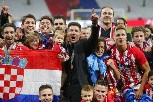 Atletico's head coach Diego Simeone, in black suit, celebrates with his players after winning the Europa League Final soccer match between Marseille and Atletico Madrid at the Stade de Lyon in Decines, outside Lyon, France, Wednesday, May 16, 2018.