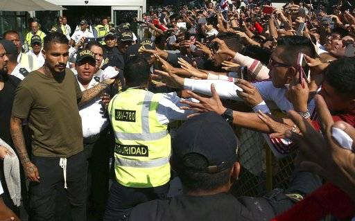 "Peru captain Paolo Guerrero, left, is greeted by fans as he arrives in Lima, Peru, Tuesday, May 15, 2018. The global footballers' union wants FIFA's help to review anti-doping rules after Guerrero was banned from the World Cup for a positive test for cocaine caused by contaminated tea. FIFPro says a 14-month ban barring the 34-year-old Guerrero from his World Cup debut is ""unfair and disproportionate."""