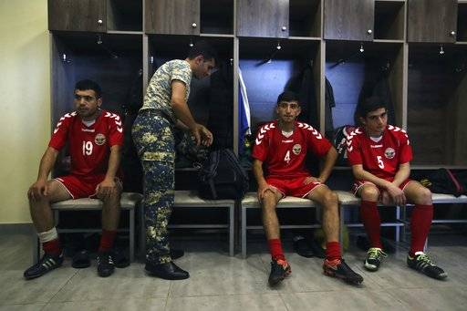 In this Friday, May 11, 2018 photo, an army officer prepares for training as his teammates listen to the coach of the soccer national team of the self-proclaimed Republic of Artsakh, in Stepanakert, the capital of the disputed territory of Nagorno-Karabakh. The ethnic Armenian team has the shirts and the shoes, and even practices five days each week on an artificial field a short distance from the center of Stepanakert. The reason for the lack of opponents has nothing to do with sports and everything to do with politics. UEFA and FIFA have a general policy of not allowing teams into competition if they don't represent an internationally recognized country or territory.