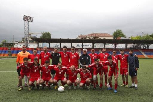 In this Friday, May 11, 2018 photo, the players and the coach of the national soccer team of the self-proclaimed Republic of Artsakh, in Stepanakert, the capital of the disputed territory of Nagorno-Karabakh. The ethnic Armenian team has the shirts and the shoes, and even practices five days each week on an artificial field a short distance from the center of Stepanakert. The reason for the lack of opponents has nothing to do with sports and everything to do with politics. UEFA and FIFA have a general policy of not allowing teams into competition if they don't represent an internationally recognized country or territory.