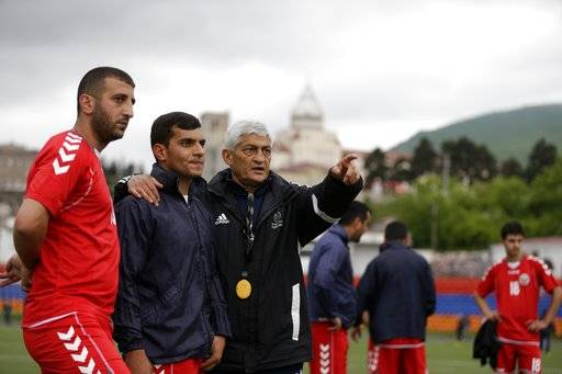 In this Friday, May 11, 2018 photo, Slavik Gabrielvan, right, the coach of the soccer national team of the self-proclaimed Republic of Artsakh gives directions to his players during a training session, in Stepanakert, the capital of the disputed territory of Nagorno-Karabakh. The ethnic Armenian team has the shirts and the shoes, and even practices five days each week on an artificial field a short distance from the center of Stepanakert. The reason for the lack of opponents has nothing to do with sports and everything to do with politics. UEFA and FIFA have a general policy of not allowing teams into competition if they don't represent an internationally recognized country or territory.