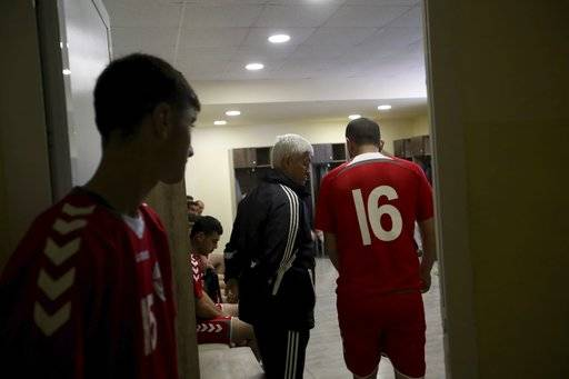 In this Friday, May 11, 2018 photo, Slavik Gabrielvan, center, the coach of the soccer national team of the self-proclaimed Republic of Artsakh speaks to his players, in Stepanakert, the capital of the disputed territory of Nagorno-Karabakh. The ethnic Armenian team has the shirts and the shoes, and even practices five days each week on an artificial field a short distance from the center of Stepanakert. The reason for the lack of opponents has nothing to do with sports and everything to do with politics. UEFA and FIFA have a general policy of not allowing teams into competition if they don't represent an internationally recognized country or territory.