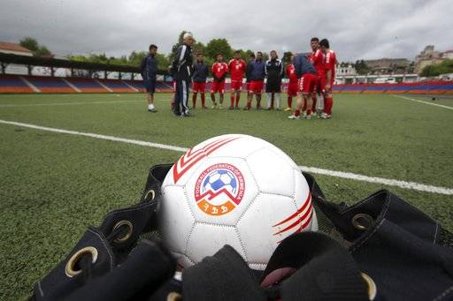 In this Friday, May 11, 2018 photo, Slavik Gabrielvan, the coach of the soccer national team of the self-proclaimed Republic of Artsakh, speaks to his players during a training session with footballs provided by the Armenian soccer federation, in Stepanakert, the capital of the disputed territory of Nagorno-Karabakh. The ethnic Armenian team has the shirts and the shoes, and even practices five days each week on an artificial field a short distance from the center of Stepanakert. The reason for the lack of opponents has nothing to do with sports and everything to do with politics. UEFA and FIFA have a general policy of not allowing teams into competition if they don't represent an internationally recognized country or territory.