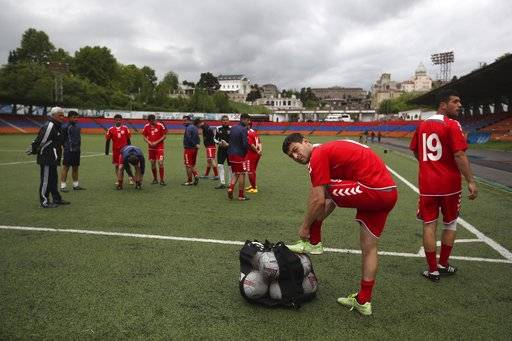 In this Friday, May 11, 2018 photo, players of the soccer national team of the self-proclaimed Republic of Artsakh prepare for a training session, in Stepanakert, the capital of the disputed territory of Nagorno-Karabakh. The ethnic Armenian team has the shirts and the shoes, and even practices five days each week on an artificial field a short distance from the center of Stepanakert. The reason for the lack of opponents has nothing to do with sports and everything to do with politics. UEFA and FIFA have a general policy of not allowing teams into competition if they don't represent an internationally recognized country or territory.