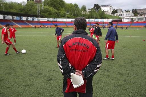 In this Friday, May 11, 2018 photo, a soccer official watches the players of the soccer national team of the self-proclaimed Republic of Artsakh during a training session, in Stepanakert, the capital of the disputed territory of Nagorno-Karabakh. The ethnic Armenian team has the shirts and the shoes, and even practices five days each week on an artificial field a short distance from the center of Stepanakert. The reason for the lack of opponents has nothing to do with sports and everything to do with politics. UEFA and FIFA have a general policy of not allowing teams into competition if they don't represent an internationally recognized country or territory.
