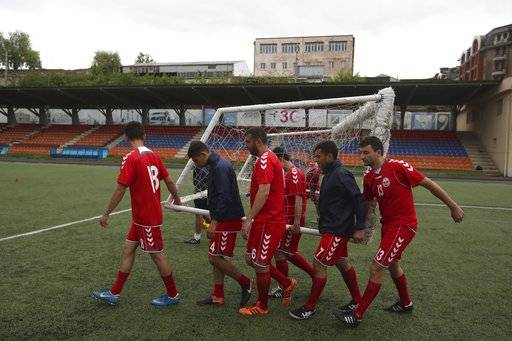 In this Friday, May 11, 2018 photo, players of the soccer national team of the self-proclaimed Republic of Artsakh carry a goalpost during a training session, in Stepanakert, the capital of the disputed territory of Nagorno-Karabakh. The ethnic Armenian team has the shirts and the shoes, and even practices five days each week on an artificial field a short distance from the center of Stepanakert. The reason for the lack of opponents has nothing to do with sports and everything to do with politics. UEFA and FIFA have a general policy of not allowing teams into competition if they don't represent an internationally recognized country or territory.