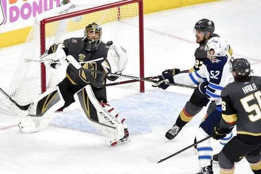 Vegas Golden Knights goaltender Marc-Andre Fleury, left, blocks a shot by Winnipeg Jets center Jack Roslovic during the second period of Game 3 of the NHL hockey playoffs Western Conference finals Wednesday, May 16, 2018, in Las Vegas.