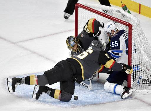 Winnipeg Jets center Mark Scheifele, right, crashes into Vegas Golden Knights goaltender Marc-Andre Fleury and left wing Erik Haula, left, during the third period of Game 3 of the NHL hockey playoffs Western Conference finals Wednesday, May 16, 2018, in Las Vegas.