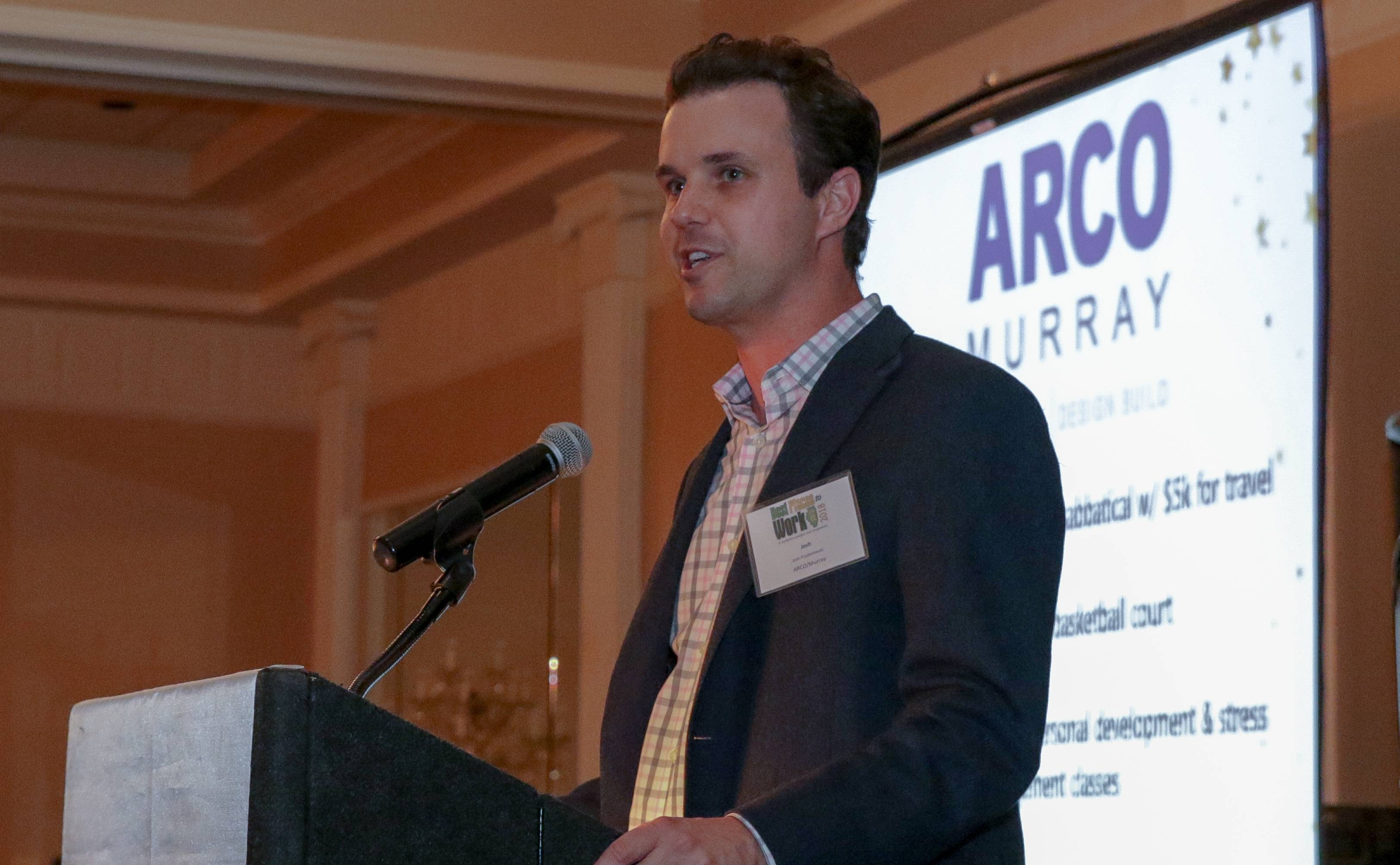 Josh Przyborowski, director of business development with Downers Grove-based ARCO/Murray National Construction Company, accepts the first-place prize for a medium-size company at the Business Ledger Best Places to Work Awards in Glen Ellyn on Thursday.