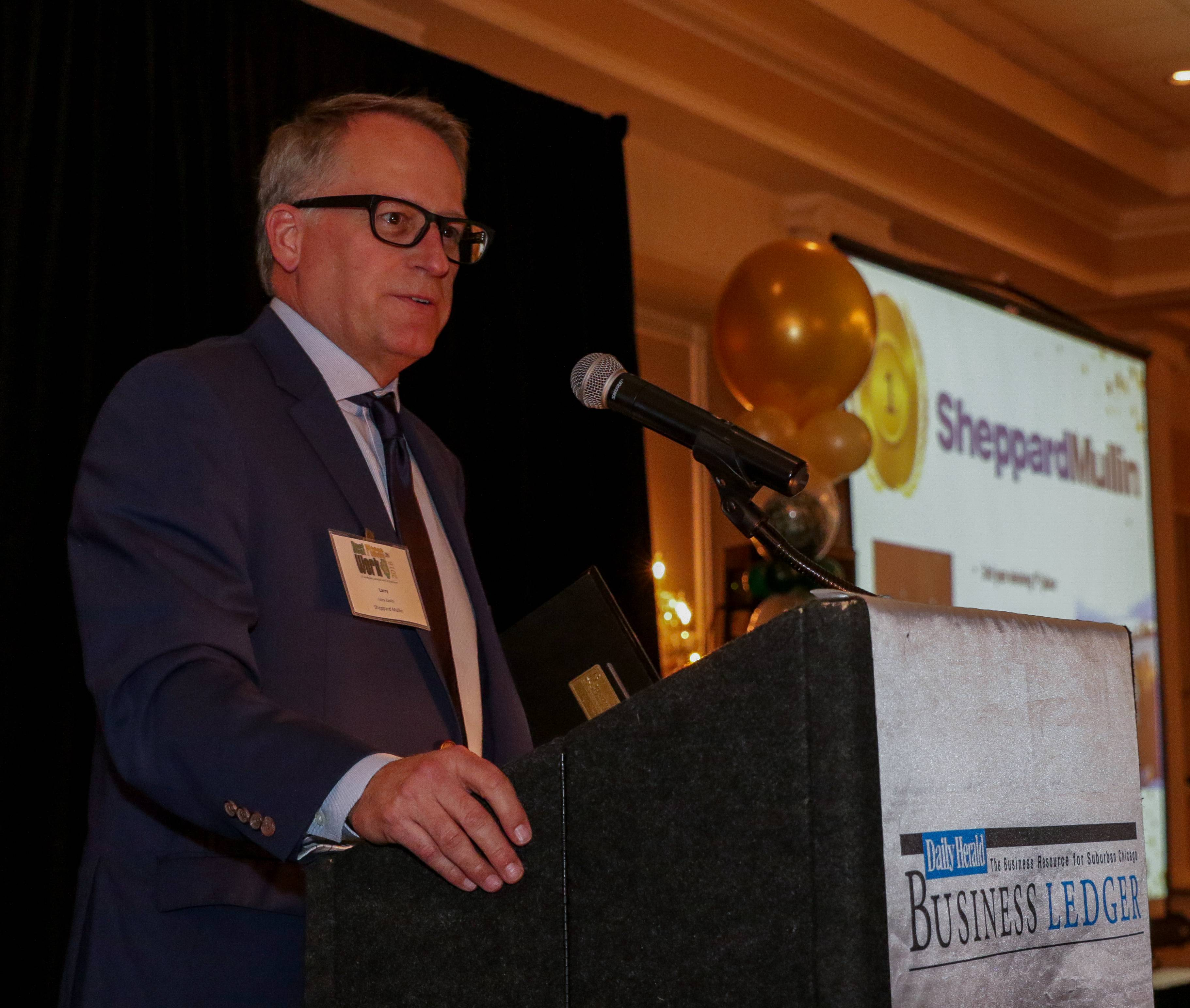 Bev Horne/bhorne@dailyherald.comLarry Eppley, Chicago Office Managing Partner with Sheppard Mullin, accepts first place for a large business at the Business Ledger Best Places to Work Awards in Glen Ellyn on Thursday.