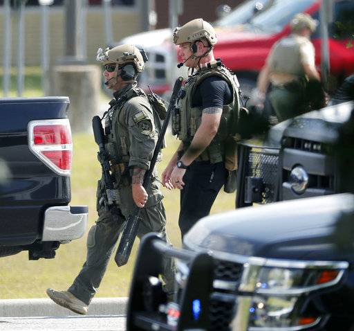 Police officers in tactical gear move through the scene at Santa Fe High School after a shooting on Friday, May 18, 2018, in Santa Fe, Texas. (Kevin M. Cox /The Galveston County Daily News via AP)