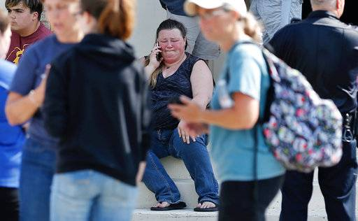 A woman reacts while making a phone call outside the Alamo Gym where parents wait to reunite with their children following a shooting at Santa Fe High School in Santa Fe, Texas, on Friday, May 18, 2018. (Michael Ciaglo/Houston Chronicle via AP)
