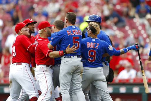 Chicago Cubs' Javier Baez, right, has a few words for Cincinnati Reds relief pitcher Amir Garrett, second from left, after striking out during the seventh inning in the first baseball game of a doubleheader, Saturday, May 19, 2018, in Cincinnati.