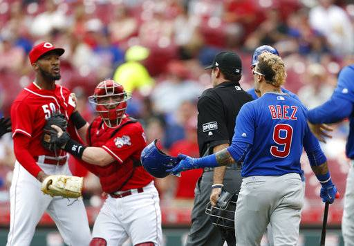 Chicago Cubs' Javier Baez (9) has a few words for Cincinnati Reds relief pitcher Amir Garrett, far left, after striking out during the seventh inning in the first baseball game of a doubleheader, Saturday, May 19, 2018, in Cincinnati.
