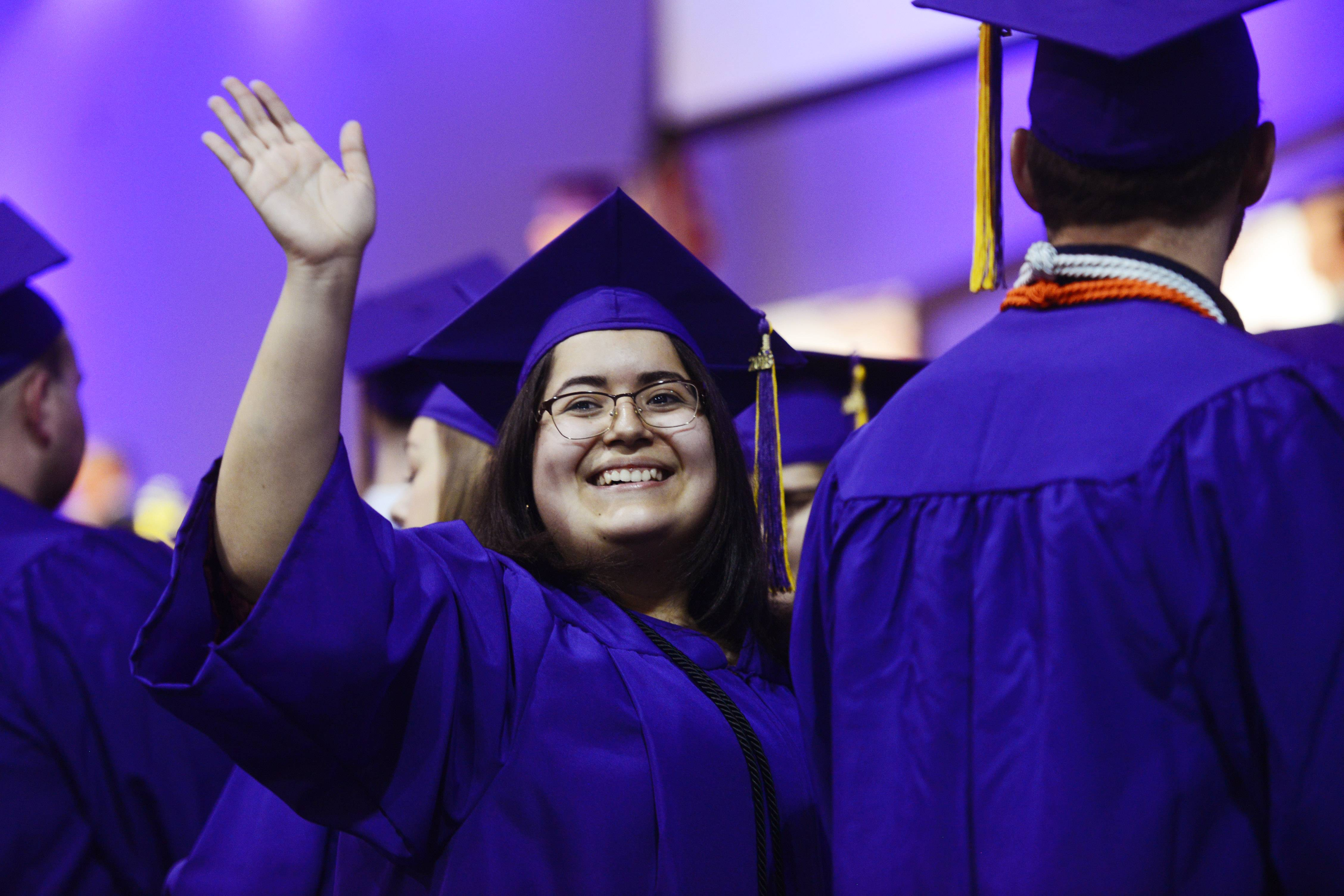 Angelica Diaz waves during the processional during the Wauconda High School graduation at the Quentin Road Bible Church in Lake Zurich Sunday.