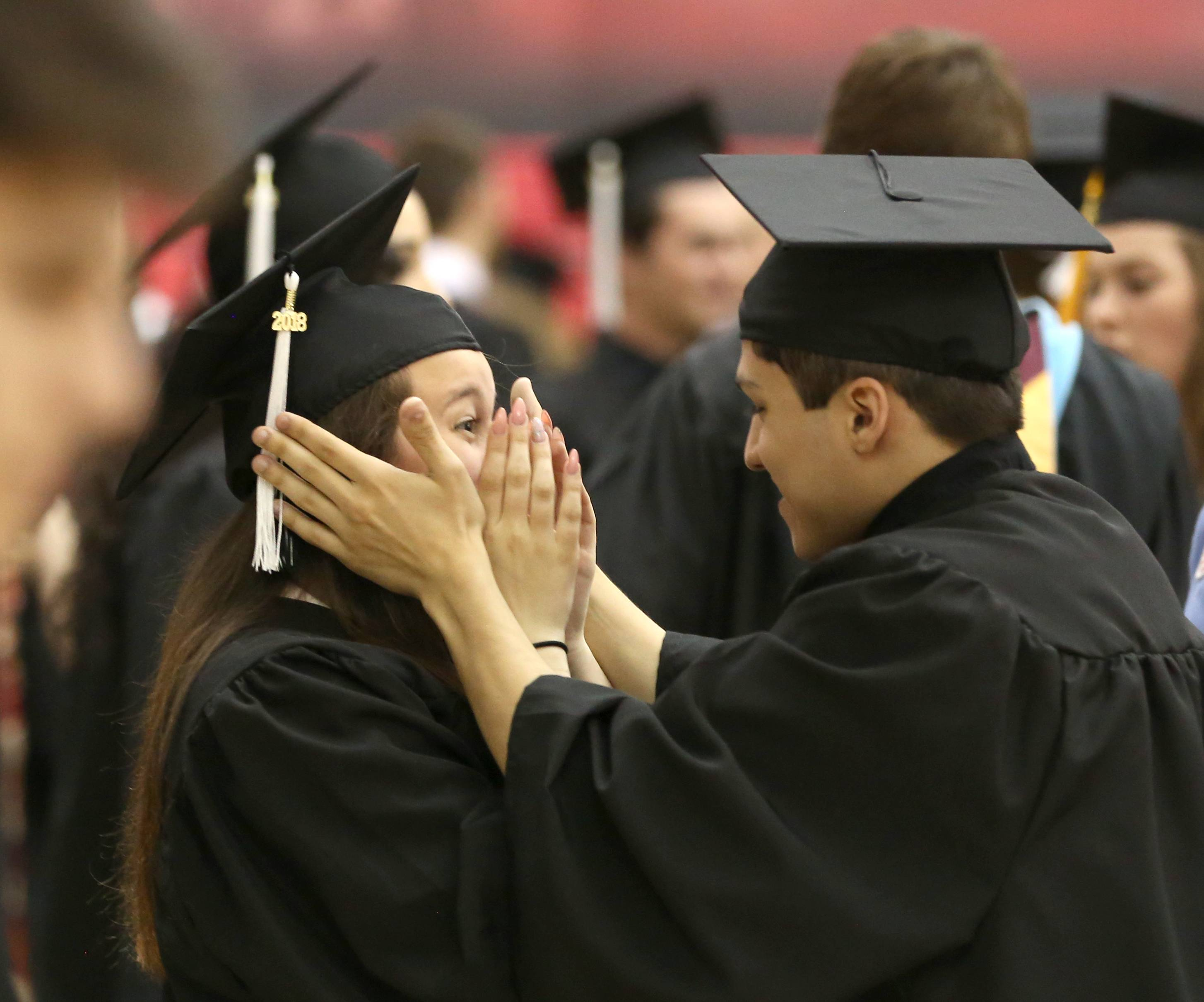 Brandon Albarran, right, and Madison Powell, left, share a moment as they prepare for the commencement program for Kaneland High School Sunday, May 20, 2018 at the Convocation Center on the campus of Northern Illinois University in DeKalb.