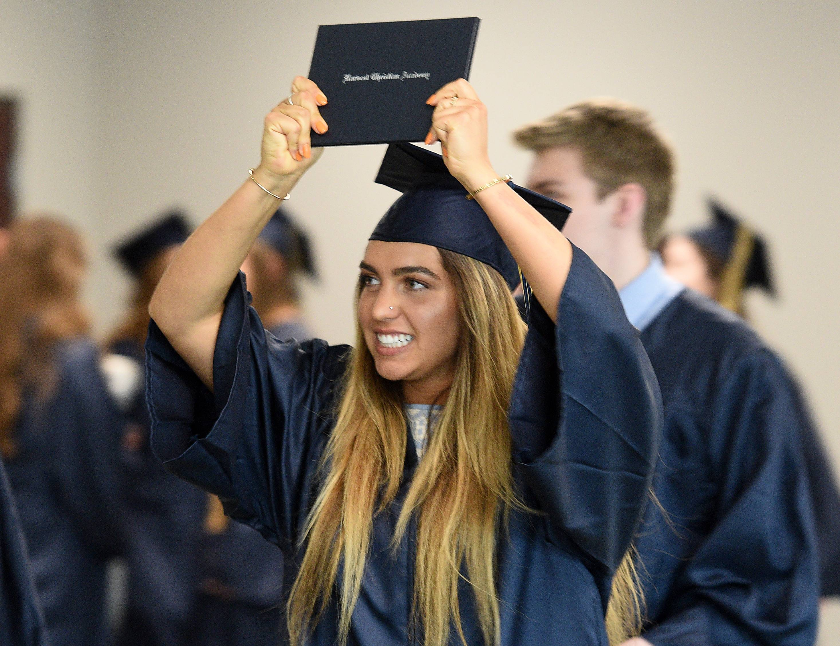 Candis Kaplan emerges victorious with her diploma held high after the Harvest Christian Academy graduation ceremony on Sunday at the school in Elgin.