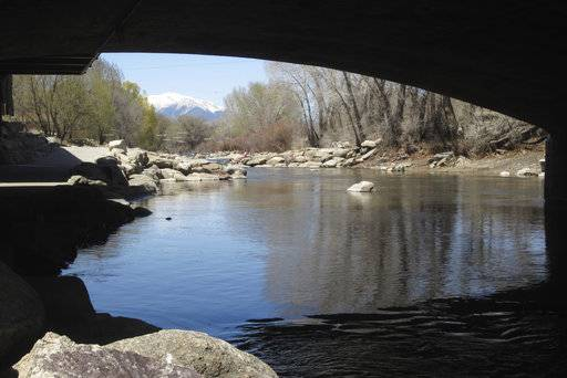 In this April 25, 2018 photo, the Arkansas River flows under a bridge in Salida, Colo., with the snow-covered Sawatch Range mountains in the background. Despite a severe drought across the Southwestern United States, there should be plenty of water this year for rafters and anglers in the Arkansas, one of the nation's most popular mountain rivers. State and federal officials say water from melting snow will surge down the river thanks to a surprisingly wet winter in the towering peaks of the Sawatch Range where the river begins.