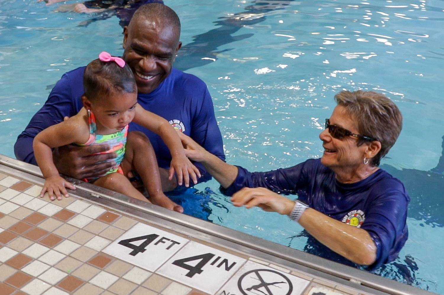 Andre Dawson holds Blair Benson, 1½, the granddaughter of Walter Payton, Monday at the grand opening of Baby Otter Andre Dawson Aquatic Center at the Westin in Lombard. On the right is Mindy York of Florida.
