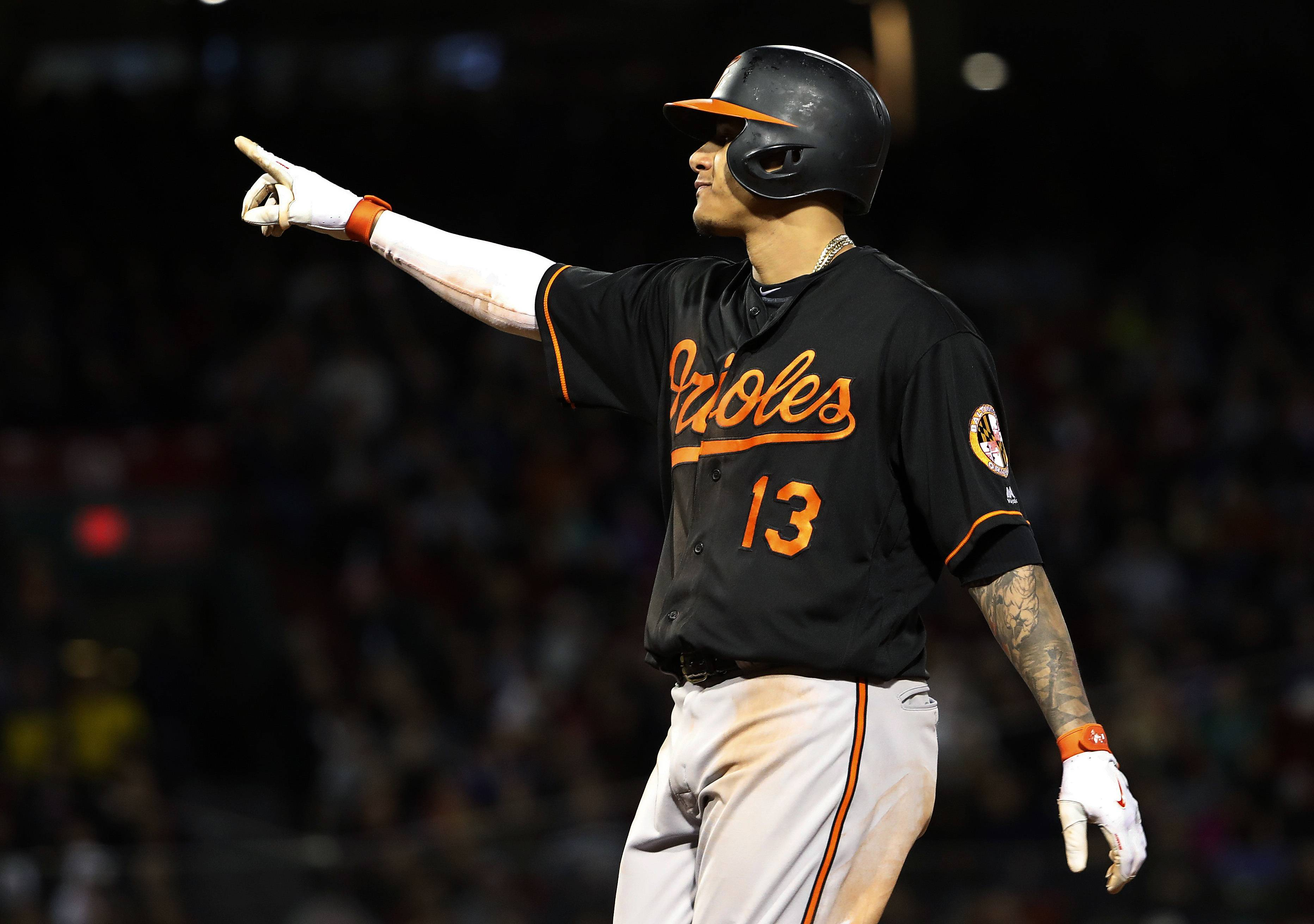 Baltimore Orioles' Manny Machado points to a teammate who scored on a two-run single during the fourth inning of the team's baseball game against the Boston Red Sox at Fenway Park in Boston Friday, May 18, 2018.(AP Photo/Winslow Townson)