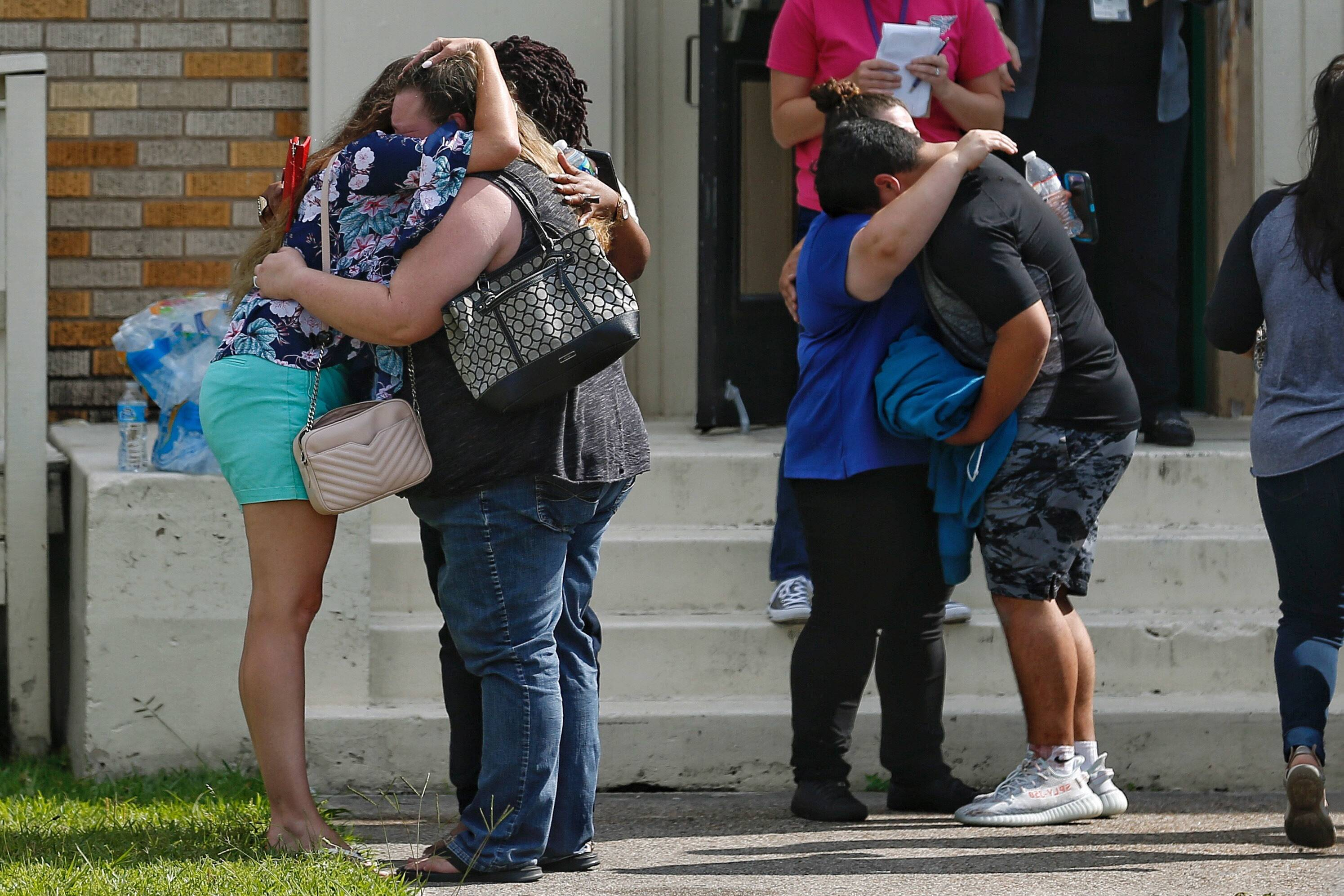 People embrace outside the Alamo Gym where students and parents wait to reunite after a shooting at Santa Fe High School on May 18 in Santa Fe, Texas.