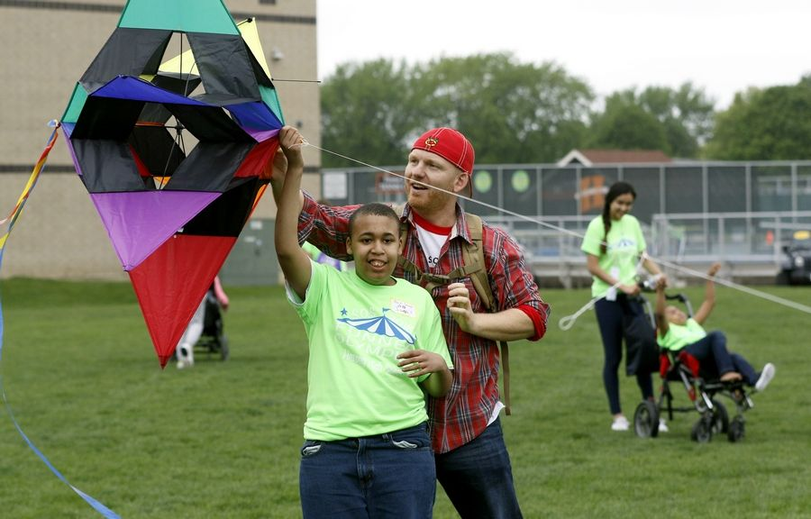Michael Seitzinger of Park School helps Isaiah, left, fly a kite Tuesday during the Funner Olympics at John Hersey High School in Arlington Heights.