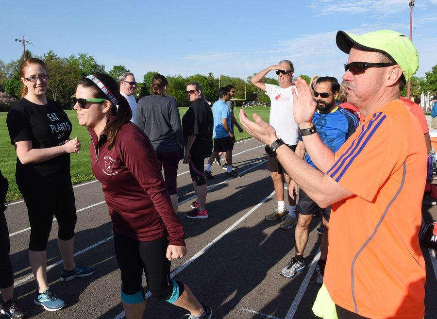 Erika Hansen of Palatine, second from left, and Tim McDonald, also of Palatine, encourage runners in the Couch to 5K program as they complete a warmup while preparing for their first race, which will take place May 27.