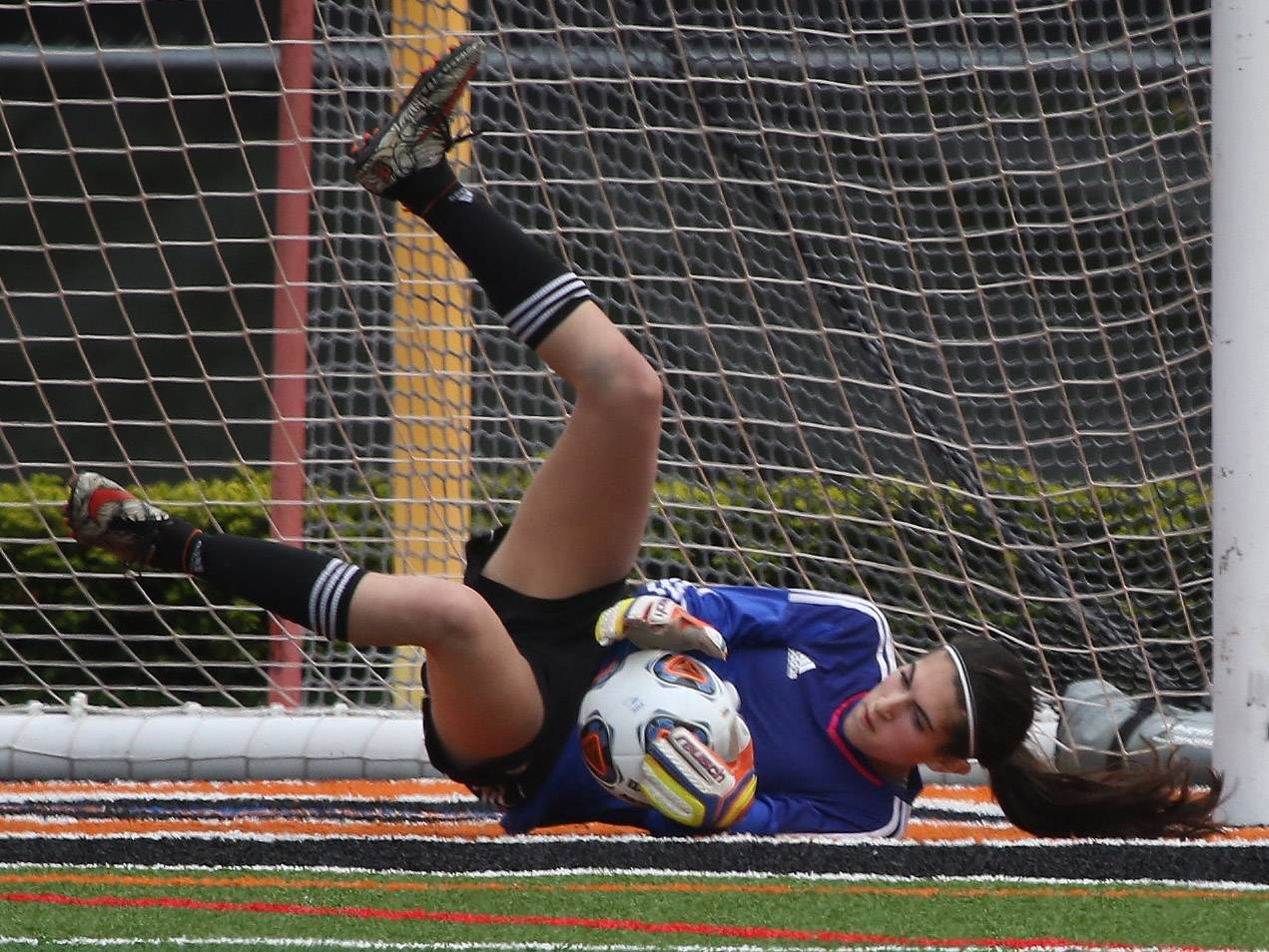 Carmel goalie Sophia Sarkis dives to stop a shot on goal against Palatine in Class 3A sectional semifinal play Tuesday in Libertyville.