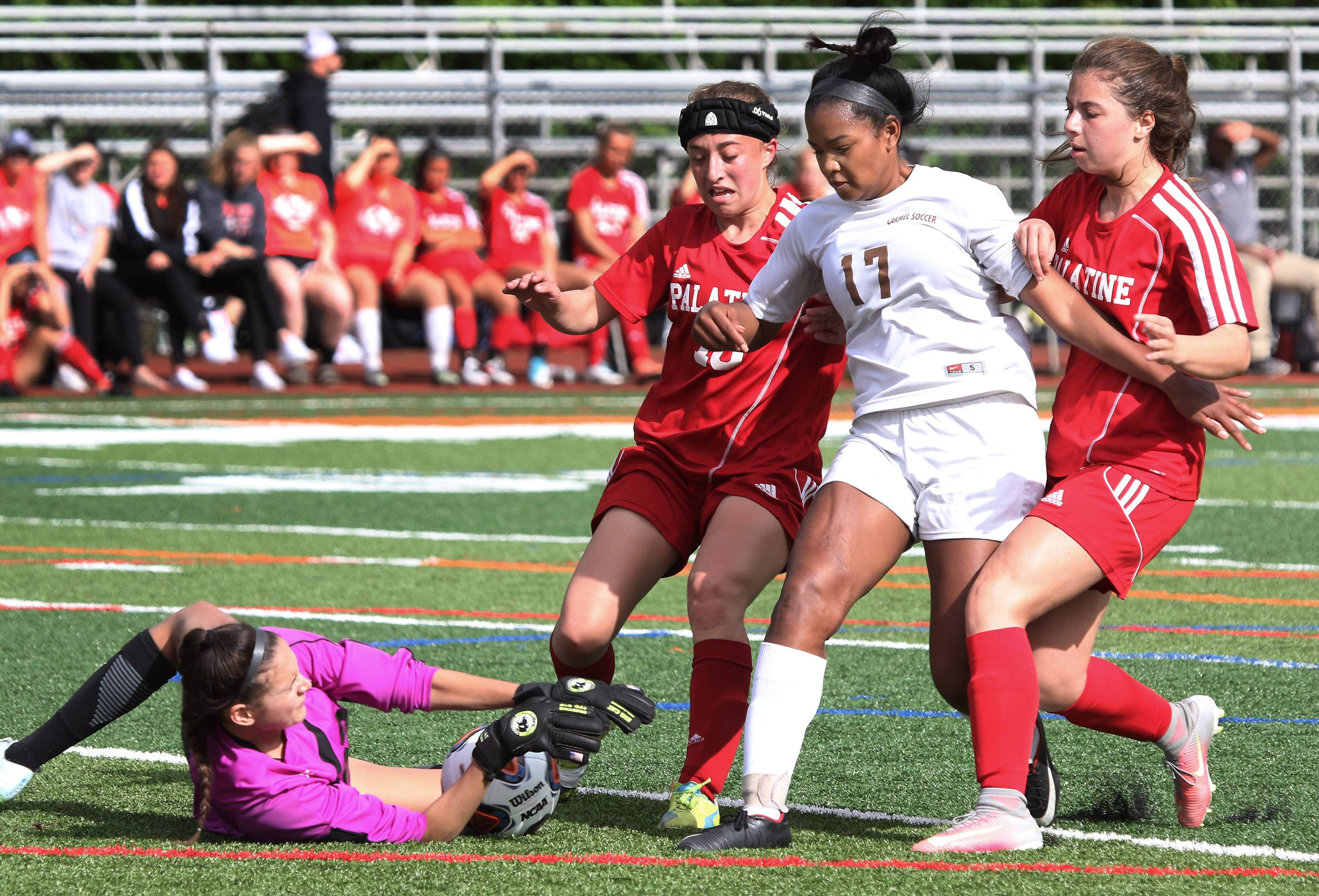 Palatine goalie Amaya Rivera stops a shot by Libertyville forward Zenaya Barnes as Palatine defenders Jamie Henning, left, and Julianna Mandarino try to stop her in Class 3A sectional semifinal play Tuesday in Libertyville.