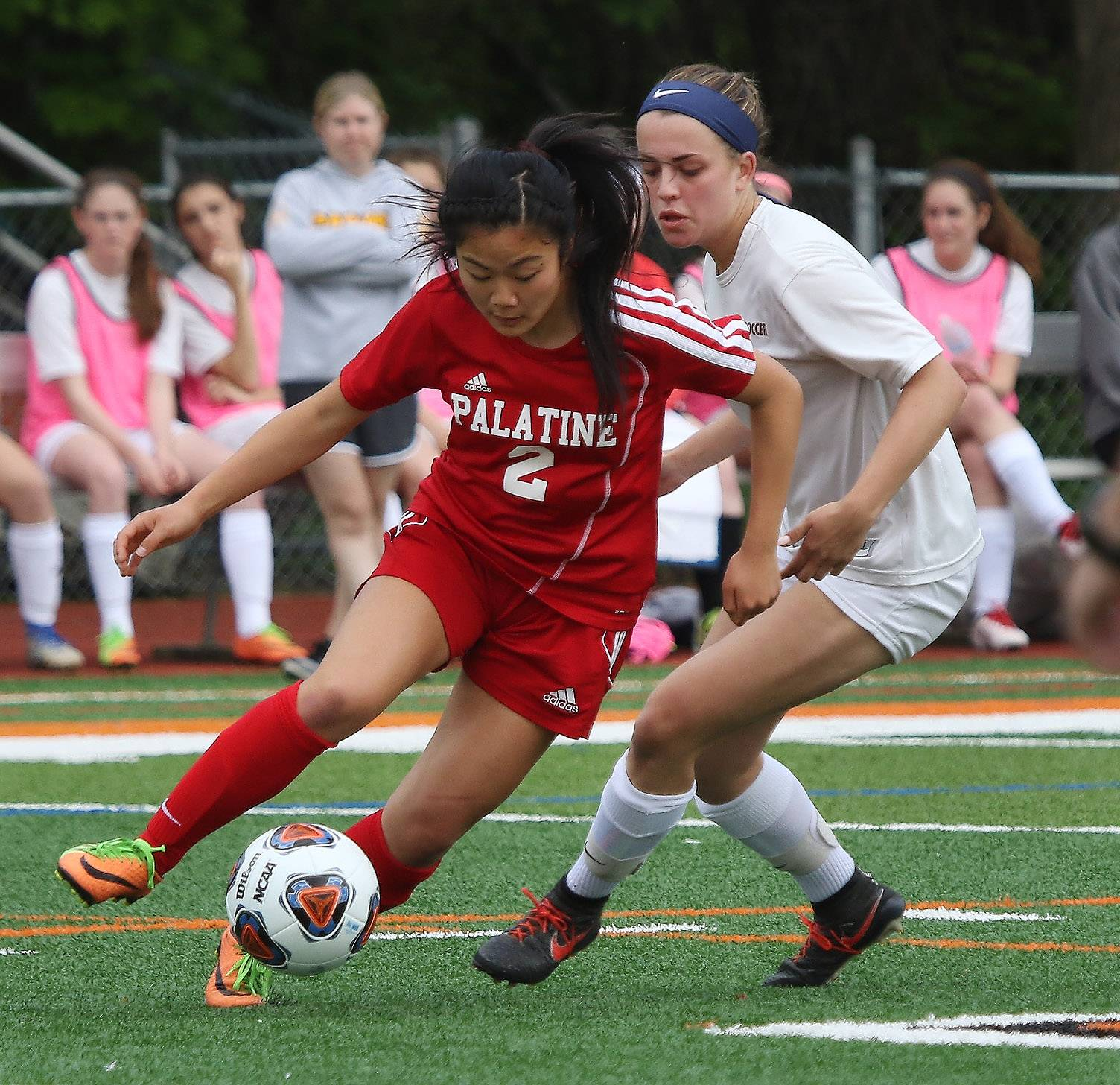 Palatine midfielder Ann Luo dribbles around Carmel forward Emma Heinrich in Class 3A sectional semifinal play Tuesday in Libertyville.