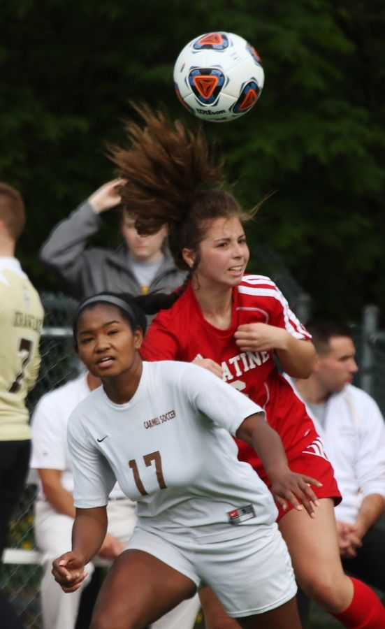 Carmel forward Zenaya Barnes battles over the ball with Palatine midfielder Julianna Mandarino in Class 3A sectional semifinal play Tuesday in Libertyville.