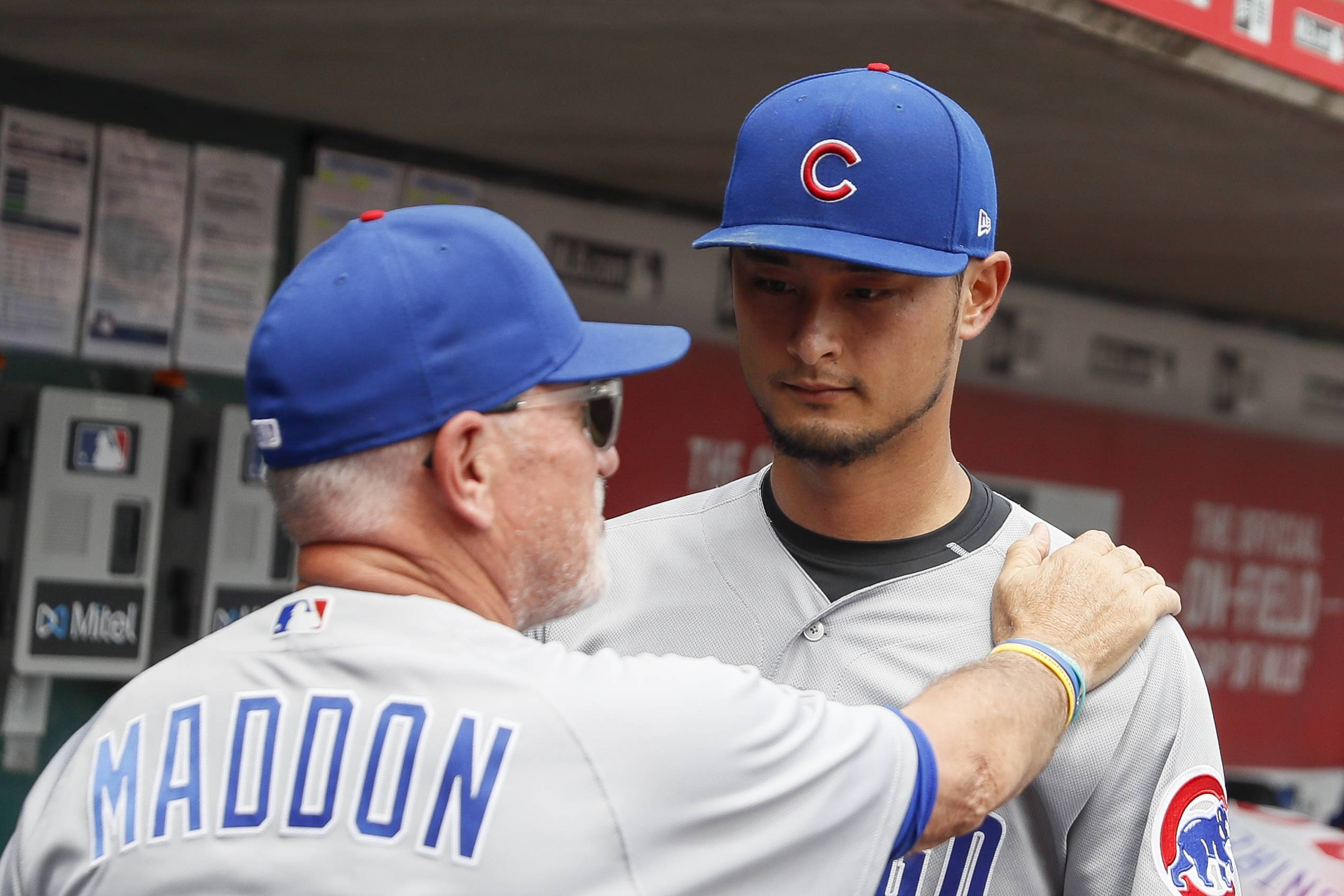 Chicago Cubs starting pitcher Yu Darvish, right, celebrates with manager Joe Maddon, left, in the dugout after closing the sixth inning of a baseball game against the Cincinnati Reds, Sunday, May 20, 2018, in Cincinnati.