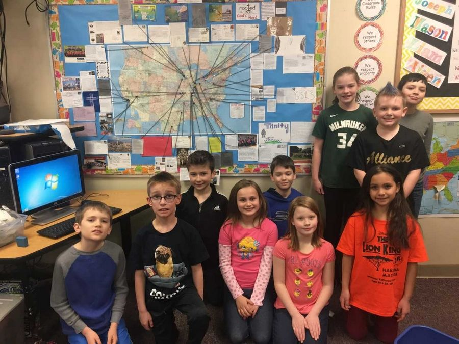 Third-graders at Immanuel Lutheran School in Batavia stand in front of a map showing the locations of the 28 Lutheran schools in the U.S. and Canada where they sent postcards.