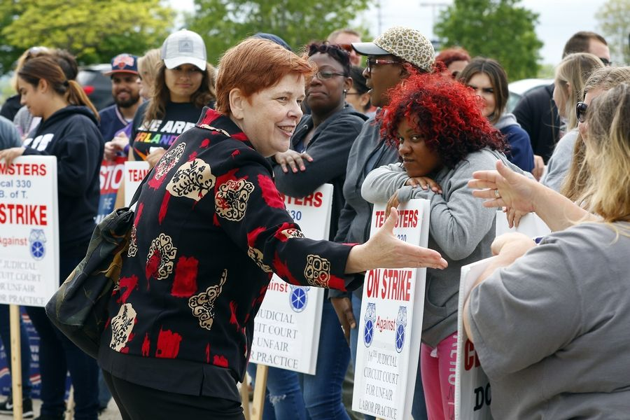 The Rev. C.J. Hawking, executive director of Arise Chicago, shakes hands Tuesday after speaking during a prayer vigil and news conference with striking Kane County probation officers and youth counselors. The strike is in its fourth week.