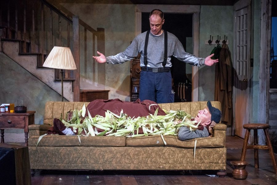 "Bradley (Timothy Edward Kane) observes his sleeping father Dodge (Larry Yando), covered by corn husks, in Sam Shepard's ""Buried Child"" at Writers Theatre."