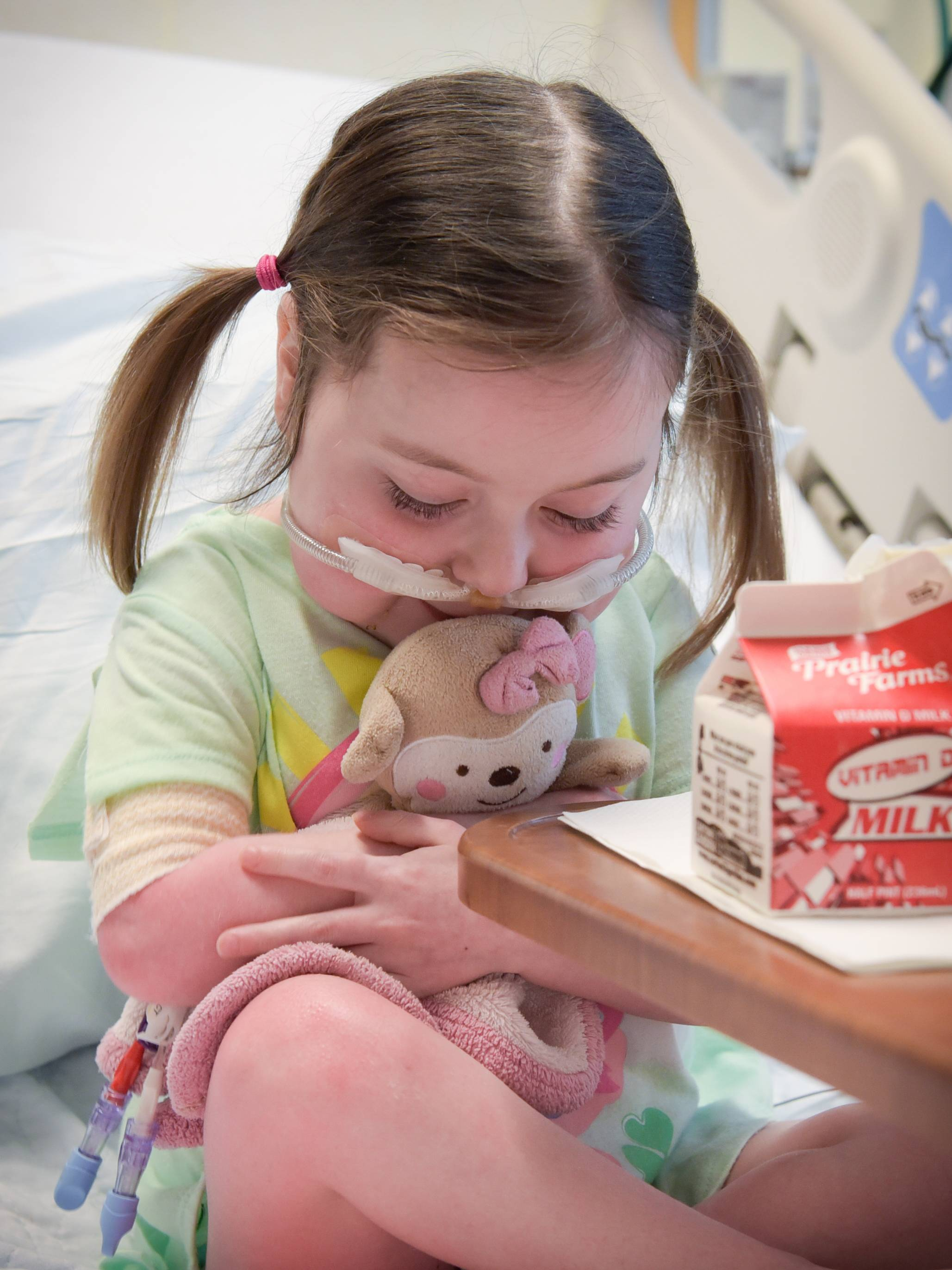 "Lucy Shannon, who received a heart transplant in April, hugs her stuffed animal she calls ""monkey baby"" in her hospital room."