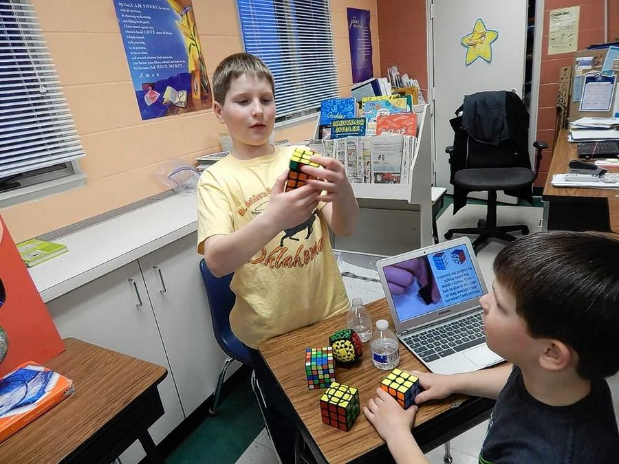 David Callender, a fifth-grader at St. Isidore Parish School in Bloomingdale, demonstrates a Rubik's cube he built from scratch and can solve in less than 30 seconds during the school's first STREAM night for students to show their projects combining the fields of science, technology, religion, engineering, arts and math.