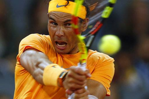 FILE - In this May 10, 2018, file photo, Rafael Nadal makes a return against Diego Schwartzman, of Argentina, at the Madrid Open tennis tournament in Madrid, Spain. Nadal will be competing in the French Open tennis tournament that begins on Sunday, May 27.