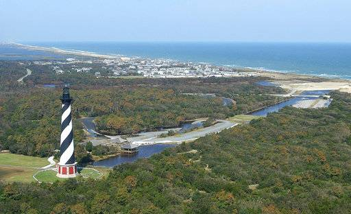 FILE - This 2003, file photo, shows the Cape Hatteras Lighthouse overlooking the Atlantic Ocean and the village of Buxton, N.C. Lighthouse Beach in Buxton is No. 6 on the list of best beaches for the summer of 2018 compiled by Stephen Leatherman, also known as Dr. Beach, a professor at Florida International University.