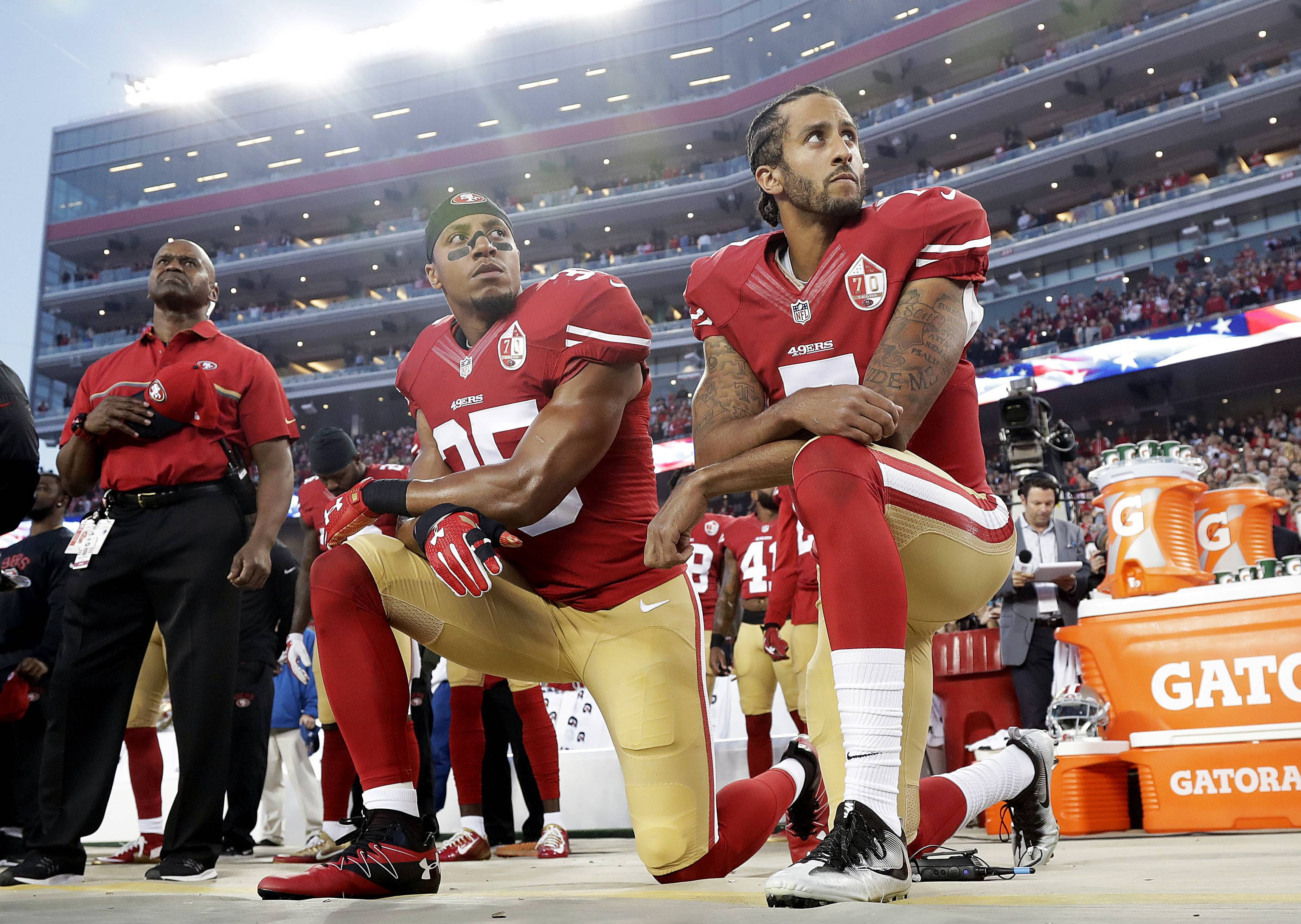 San Francisco 49ers safety Eric Reid (35) and quarterback Colin Kaepernick kneel during the national anthem. NFL owners hope a new anthem policy keeps fans from focusing on politics and puts their attention on the football being played.