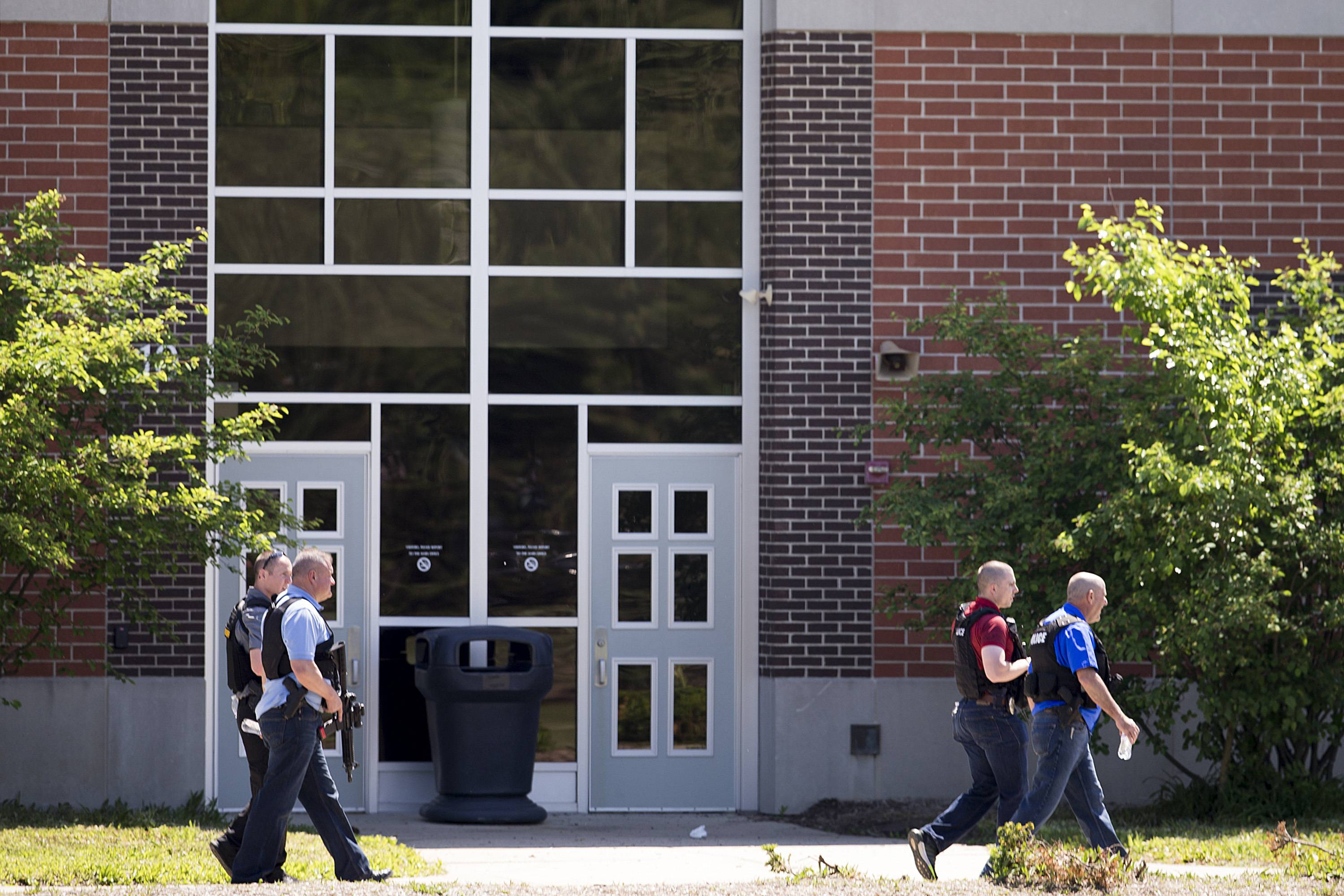 Law enforcement officers walk Friday outside Noblesville West Middle School in Noblesville, Indiana, after a shooting. A male student opened fire at the suburban Indianapolis school wounding another student and a teacher before being taken into custody, authorities said.